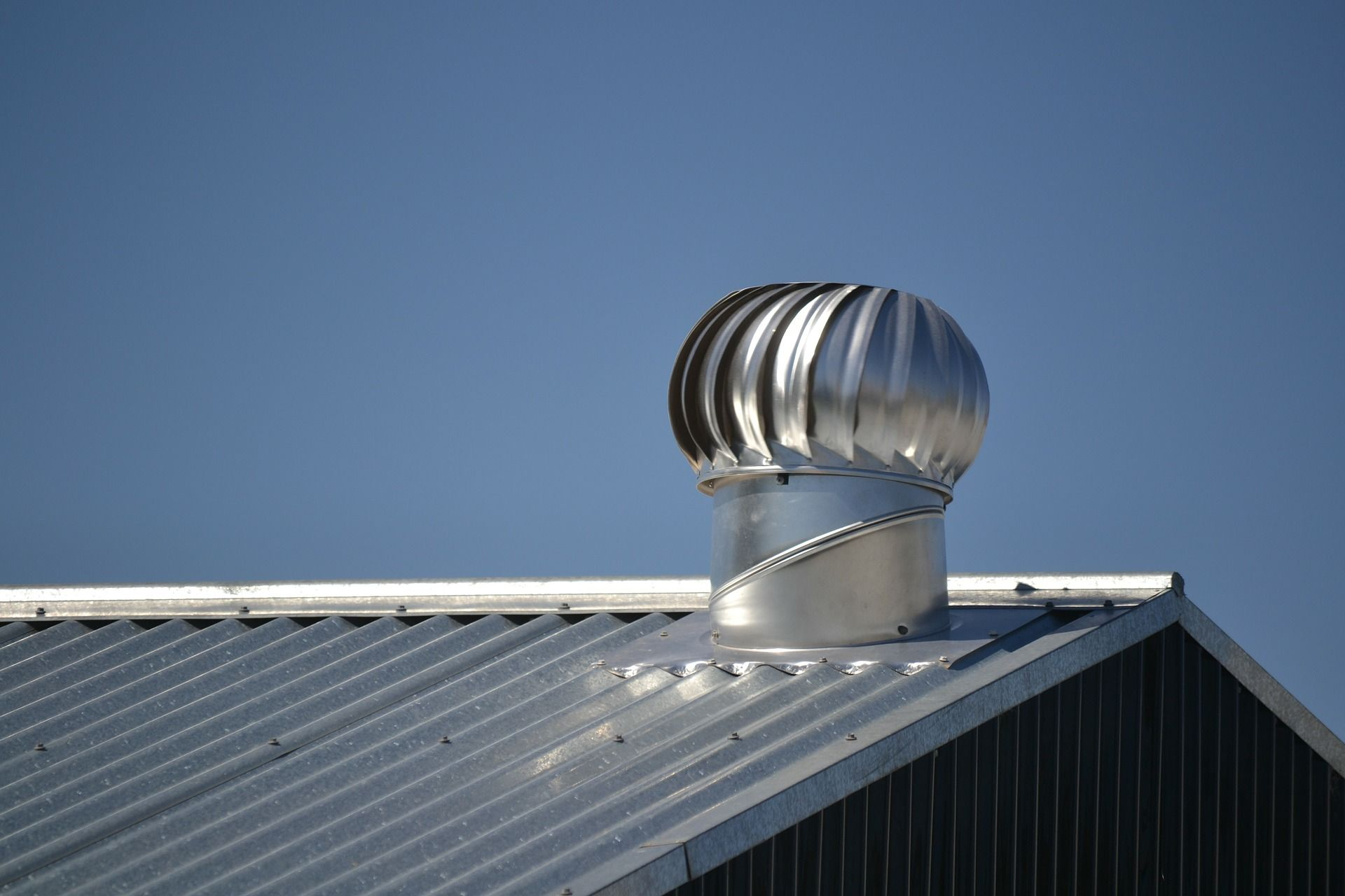Image of a shiny turbine roof vent on a shiny metal roof.